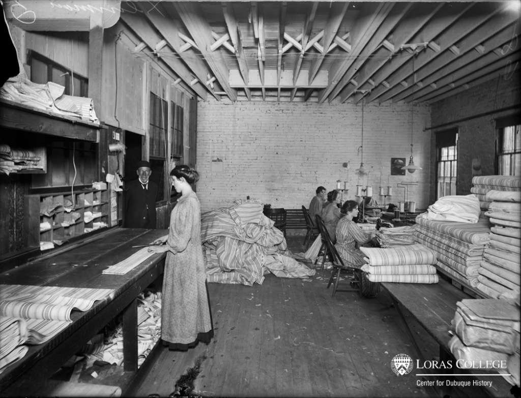 At the mattress factory, women cut and sewed the mattress ticking under the watchful eye of the male owner. They earned from $4 to $6/week. In a separate part of the factory, the men filled the mattresses and stitched them together, earning from $6 to $15/week. (Dubuuque Mattress Factory, 1912)