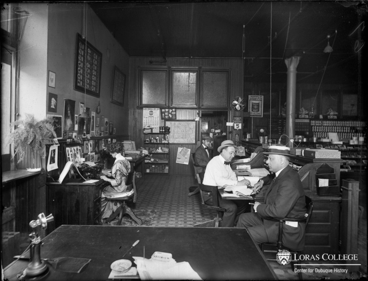In 1912, men continued to dominate the clerical labor force. However, as employers recruited trained women for clerical jobs, the status and wages associated with clerical jobs dropped. (Office at the McFadden Coffee and Spice Company)